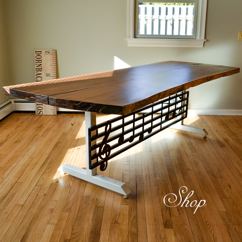 black walnut dining table with a handmade metal base in the shape of a music staff