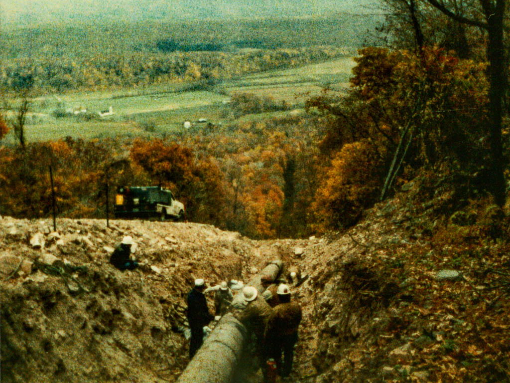 A view of men welding pipeline on top of a mountain
